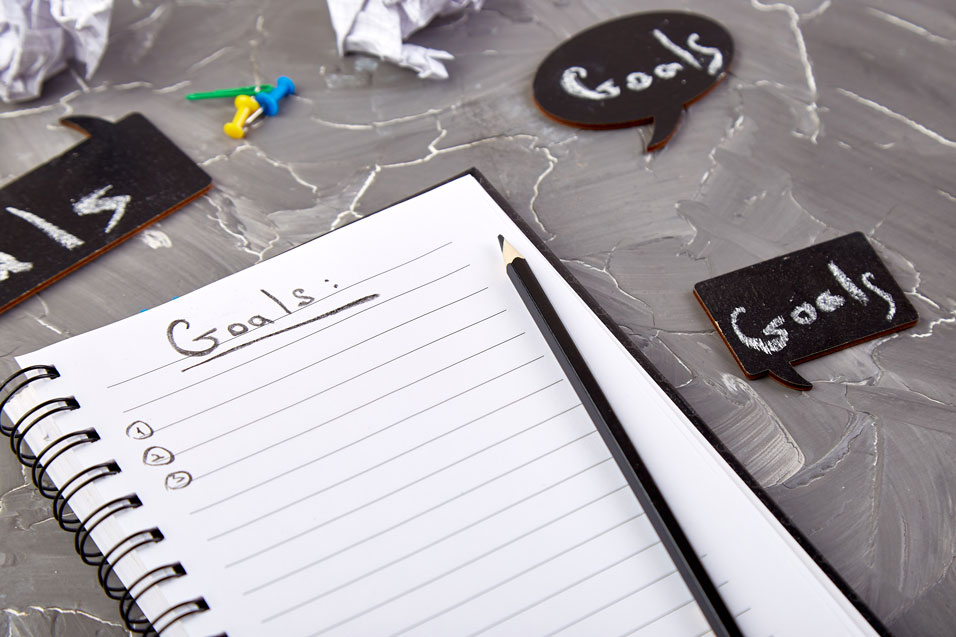A notepad with the word 'Goals' written in black pencil.